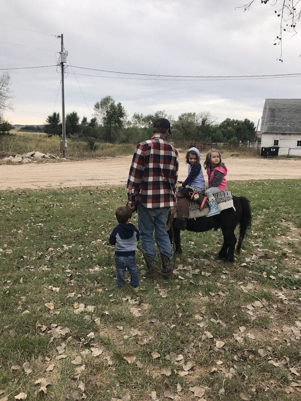 dad, 3 little children, and a mini horse on a family ranch with a white barn in the background
