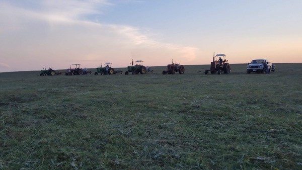 row of tractors lined up at dusk with sunset in a hay field