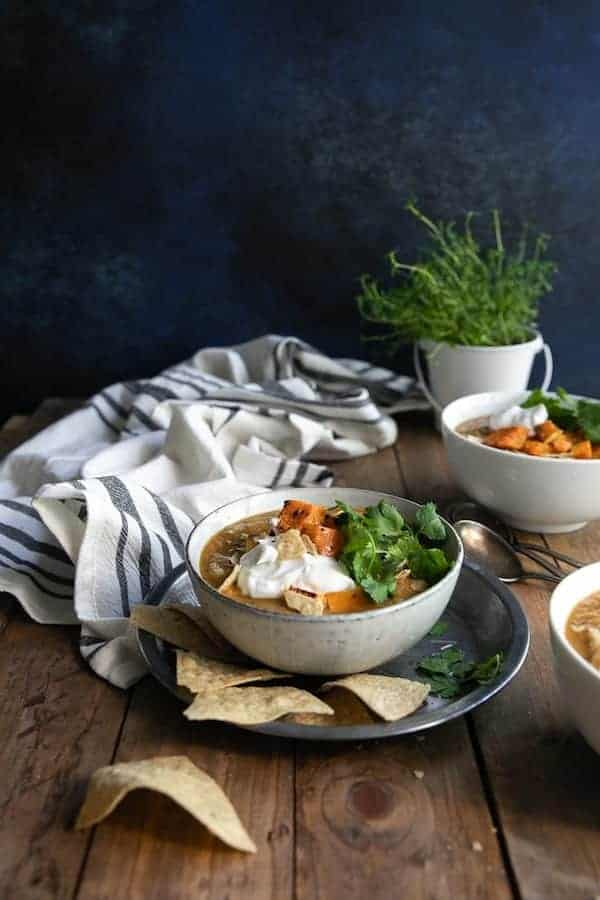 bowls of the squash and black bean soup in white bowls and sitting on a rustic wooden table