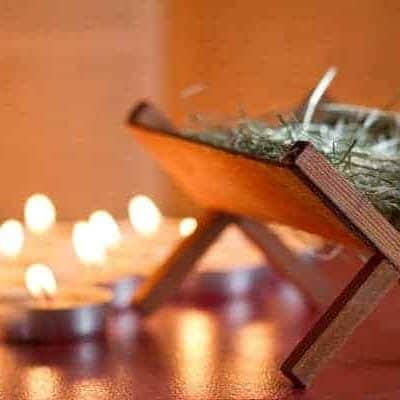 empty manger with lit candles in the background