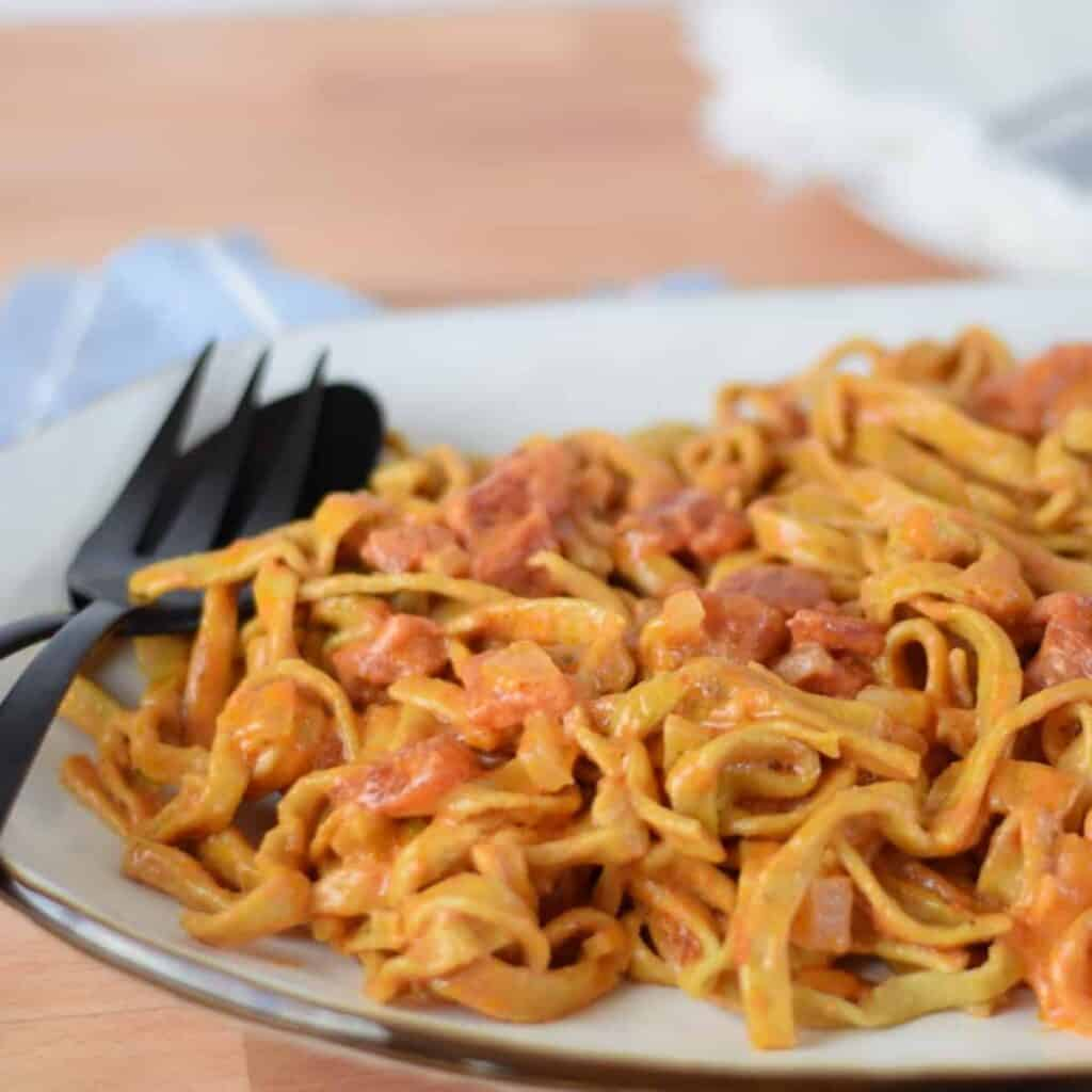 pasta with red sauce on a white platter with black serving utensils