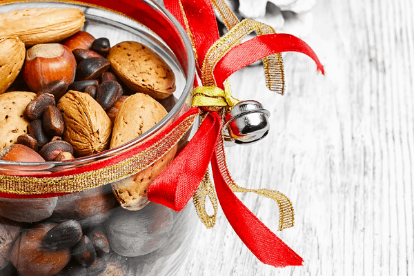 jar of mixed nuts with red and gold ribbons wrapped around top and a jingle bell tied on