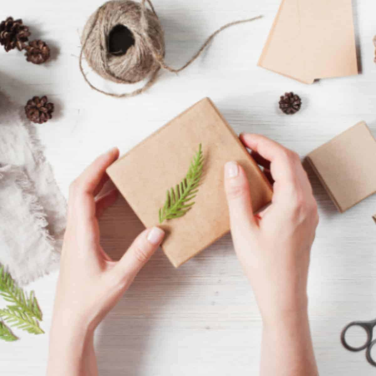 flat lay of brown gift box with twine, pine cones, and green herbs