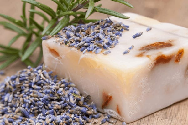 homemade bar of soap on a wood board with lavender on top