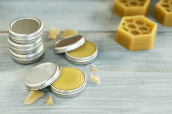 homemade lip balms in tins on gray wooden table