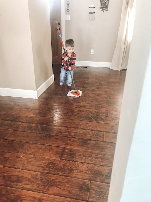 little boy using a mop on hardwood floors