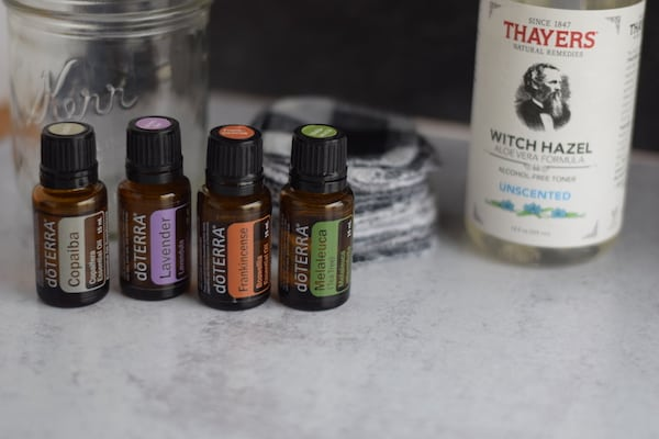 four essential oil bottles with with hazel