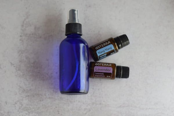 blue glass spray bottle, ylang ylang, and lavender essential oils