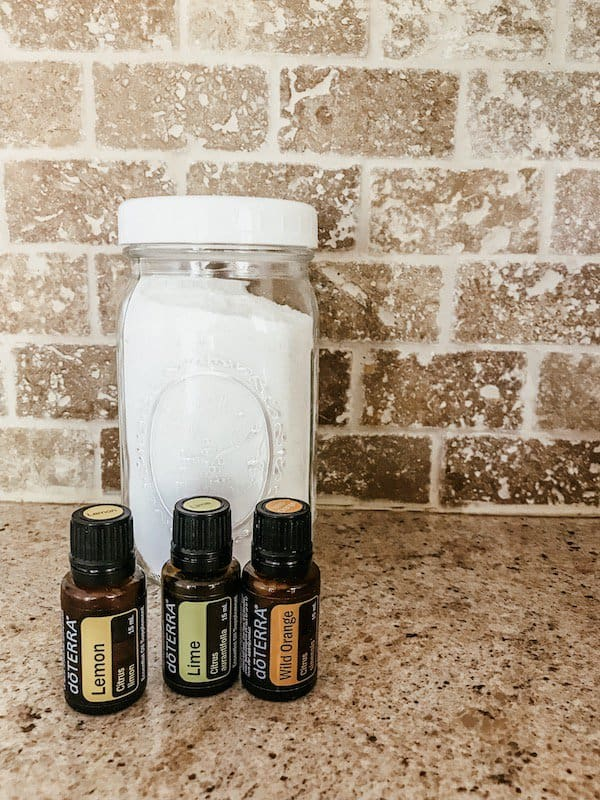 laundry detergent in a mason jar with essential oil bottles on countertop