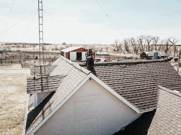 husband sitting on house roof with drone controller