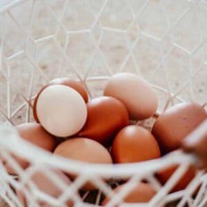 farm fresh chicken eggs in a white wire basket