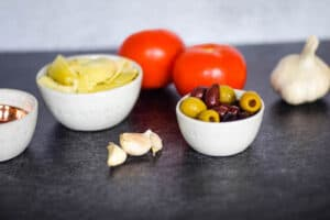 fresh olives, artichokes, tomatoes, garlic in little white bowls