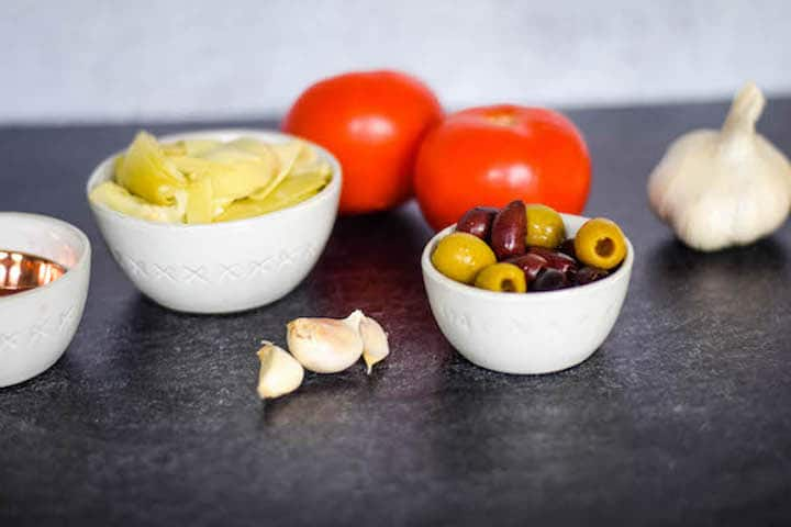 tomatoes, olives, artichokes in small white bowls