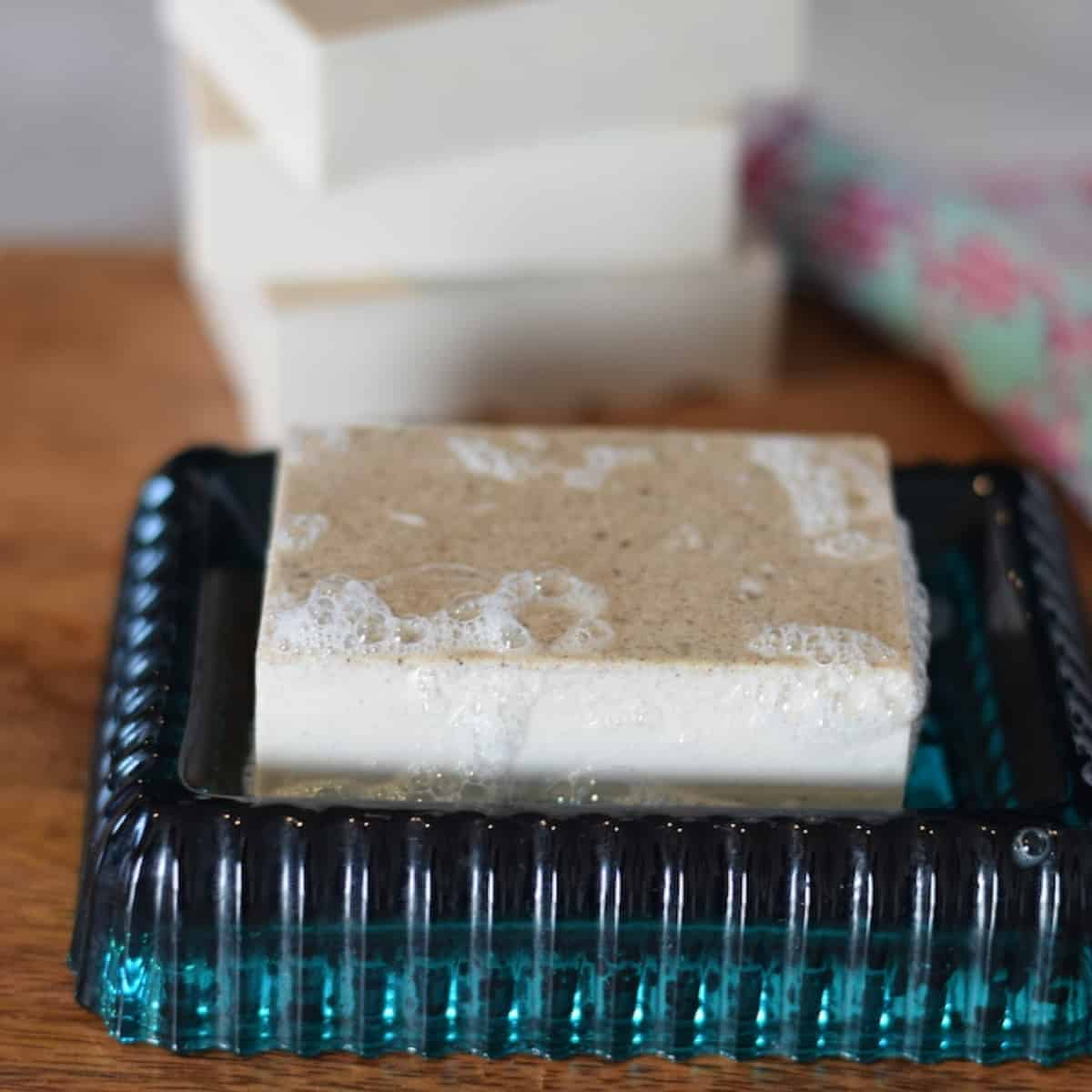 homemade bar of soap on a wood board and teal soap dish