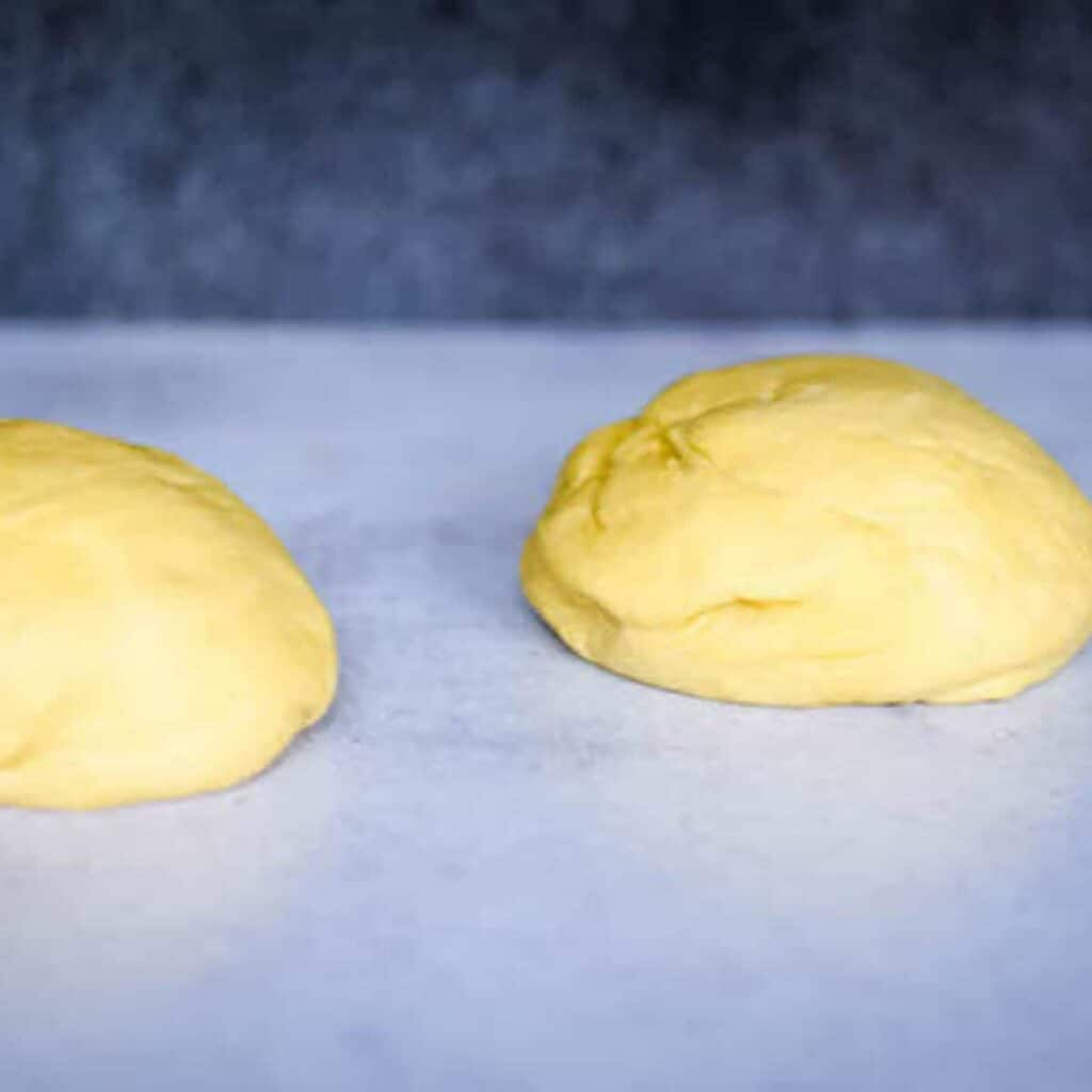 two pizza dough balls on countertop