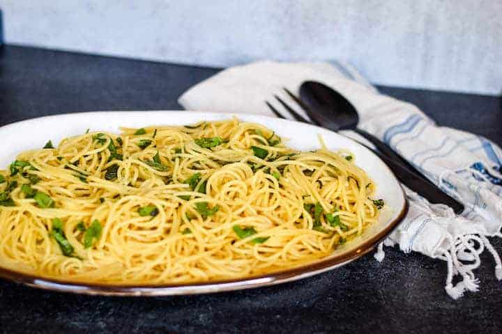 pasta on a white platter with fresh herbs