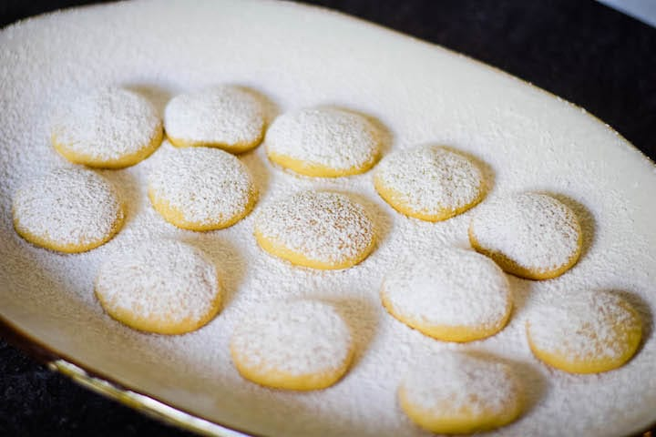 butter cookies on a white platter with a dusting of powdered sugar