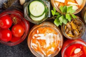 canning and preservation jars of vegetables on a black countertop