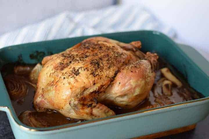whole Mediterranean roast chicken in a blue baking dish