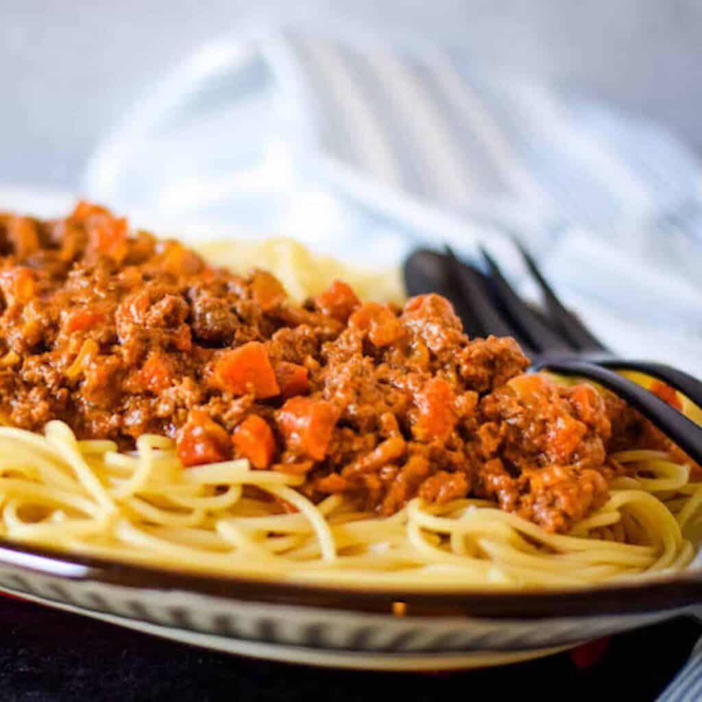 beef ragu over spaghetti on a platter