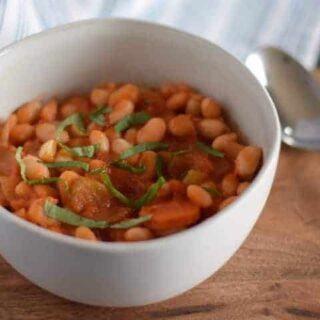 simple greek bean soup in a white bowl with a spoon