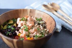 salmon grain bowl recipe in a wooden bowl