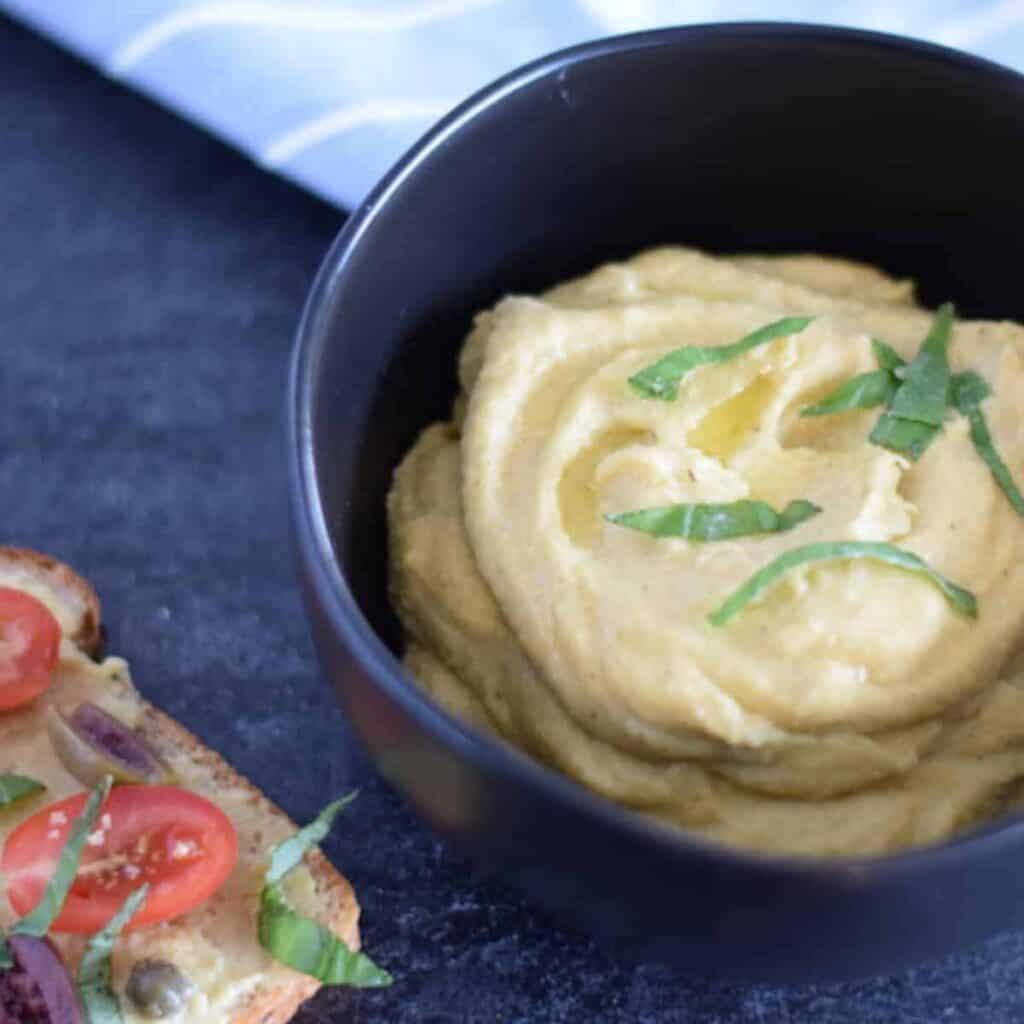spicy garlic hummus in black bowl