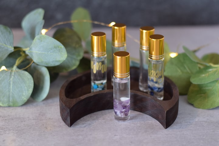 essential oil roller bottles on a decorative half moon wooden tray