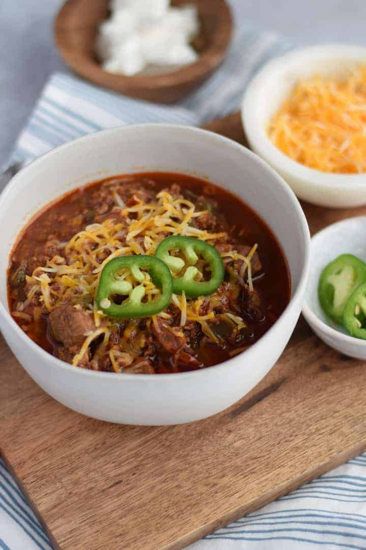 keto chili in a white bowl with garnishes in small bowls