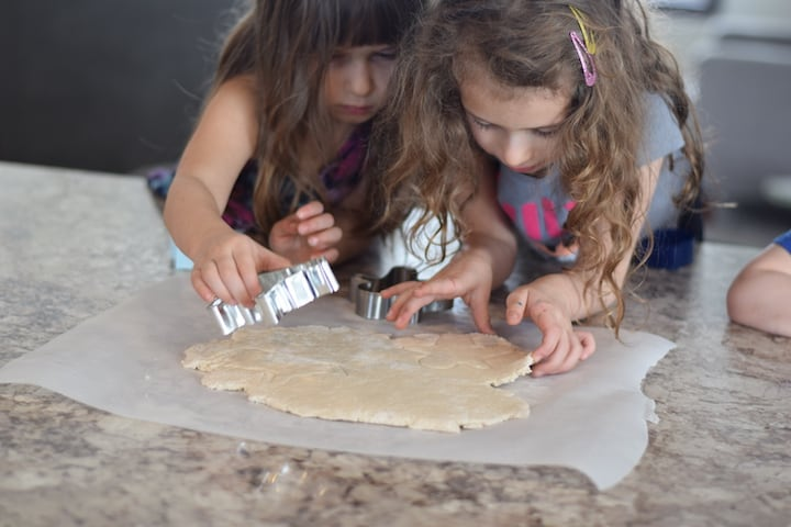 two little girls using cookie cutters to make salt dough ornaments