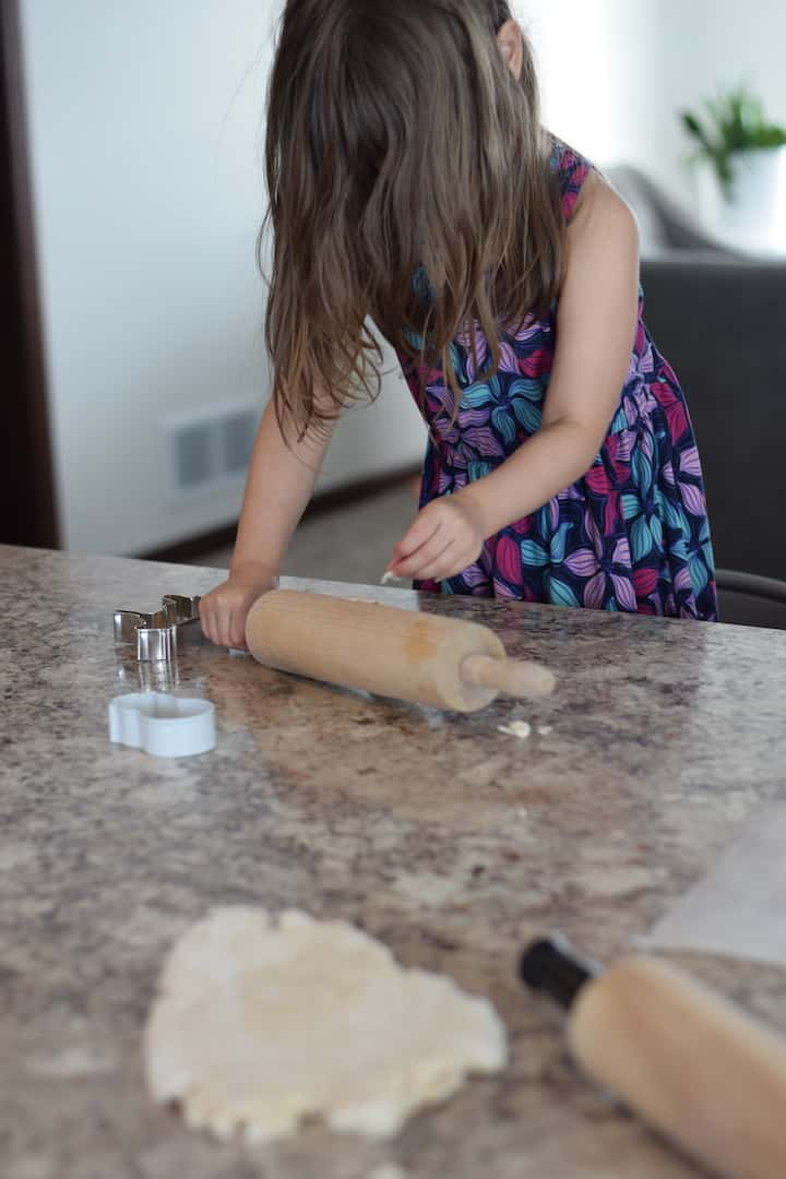 little girl rolling out salt dough on countertop