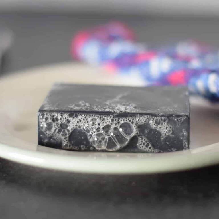 charcoal soap bar on a white plate with suds