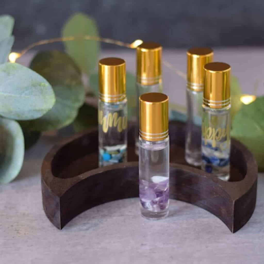 essential oil roller bottles on a half moon wooden stand