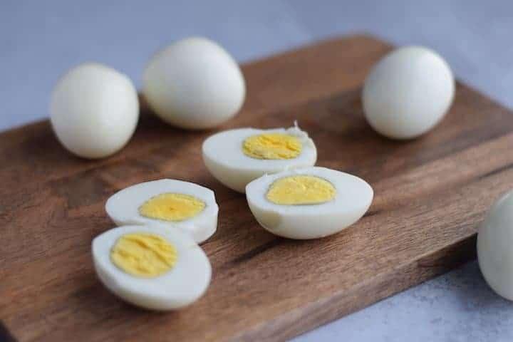 Ninja Foodi hard boiled eggs on a wooden cutting board