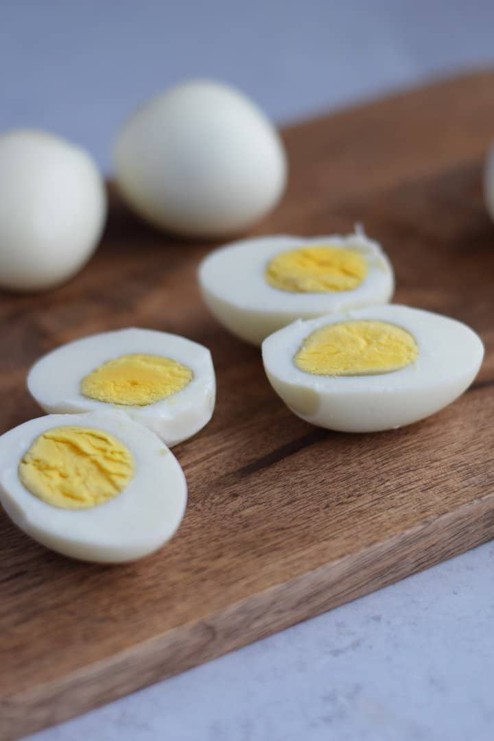 hard boiled eggs peeled and resting on cutting board