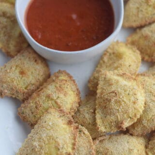 Ninja Foodi fried ravioli on a white platter with marinara sauce in a bowl
