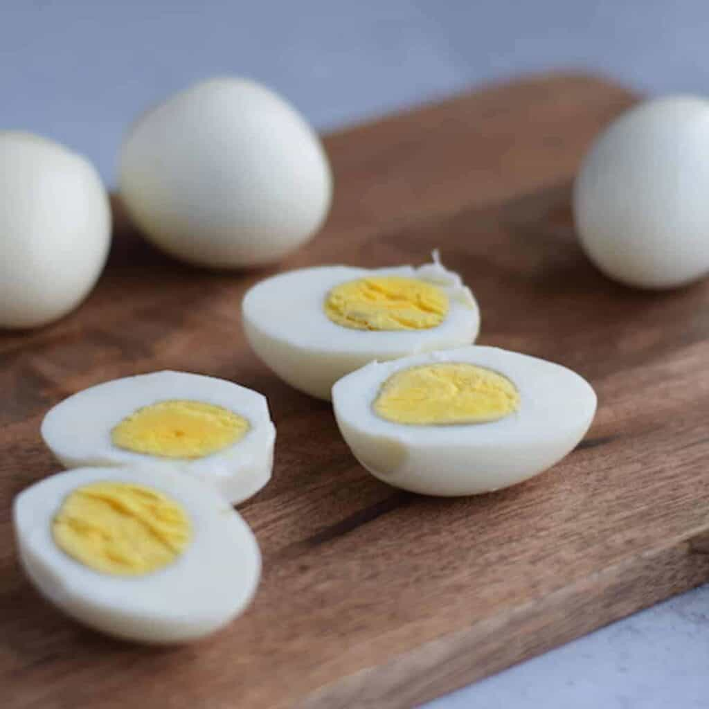 Ninja Foodi hard boiled eggs on a wooden cutting board