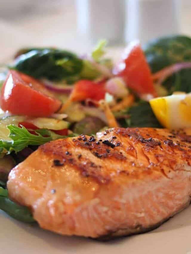 salmon over salad on a white plate