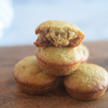 honey banana muffins stacked on wooden cutting board