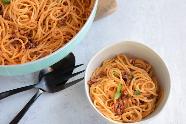 light blue skillet and small white bowl with sun dried tomato cream sauce over spaghetti noodles
