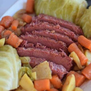 Ninja Foodi corned beef and cabbage on a white platter with potatoes and carrots