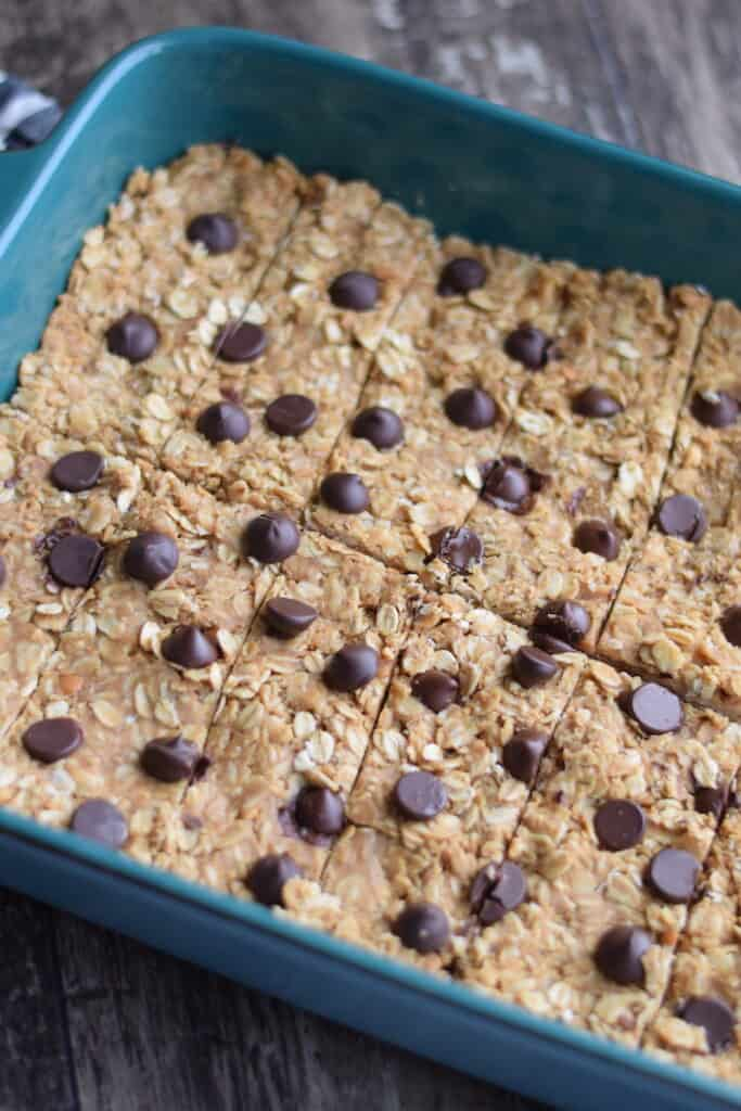 cutting the granola bars inside a blue baking dish