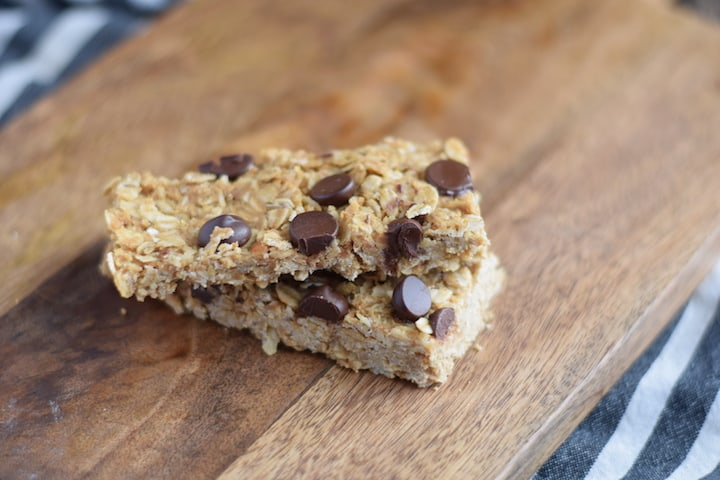 closeup image of granola bars with chocolate chips on a wooden cutting board