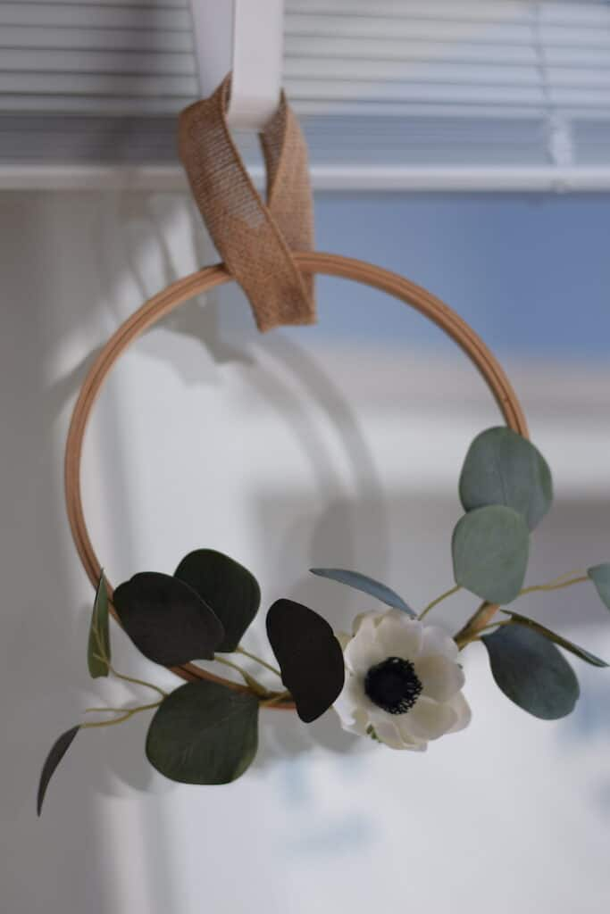 embroidery hoop wreath with white flower and eucalyptus hanging on door with hook