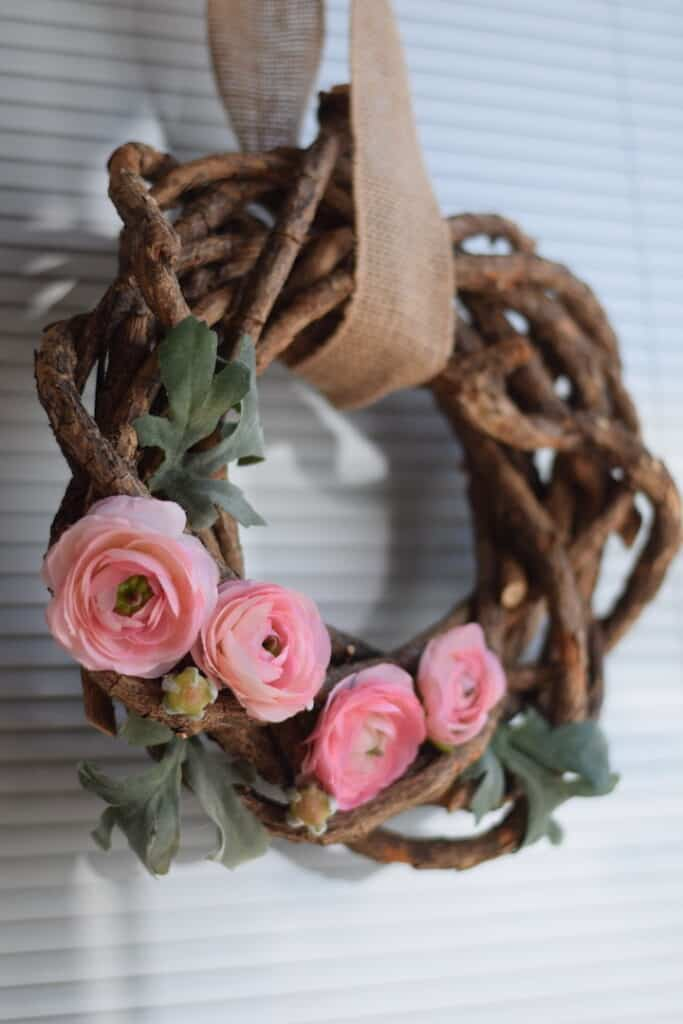 pink floral wreath with rustic branches hanging on door