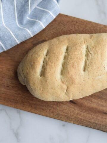 fresh baked italian bread loaf on a wooden cutting board