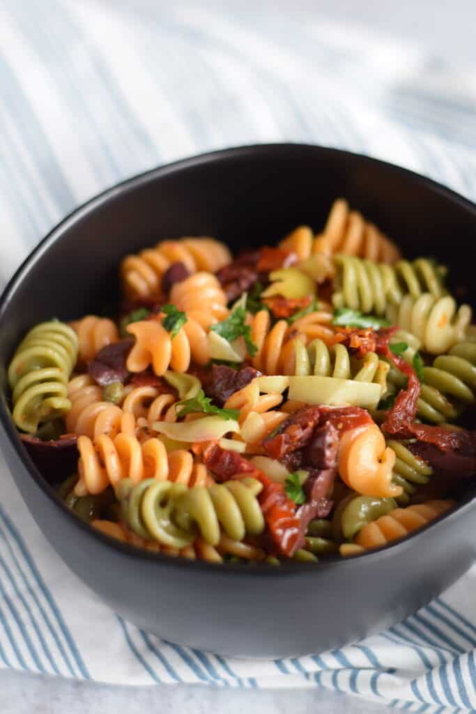 Mediterranean pasta salad in a black bowl
