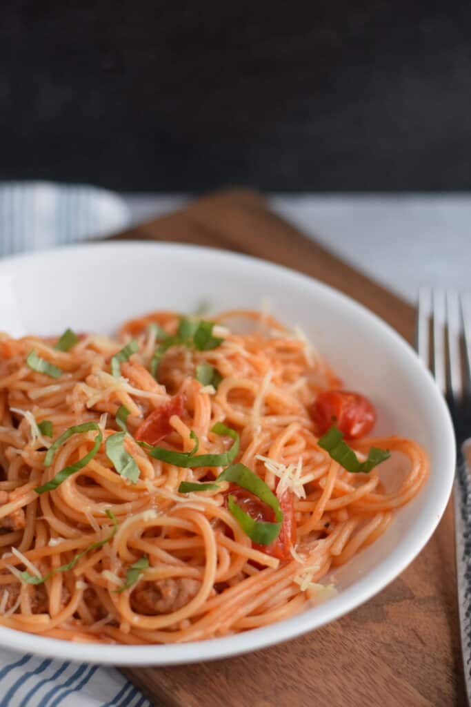 Ninja Foodi spaghetti with sausage in a pasta bowl and on a wooden cutting board