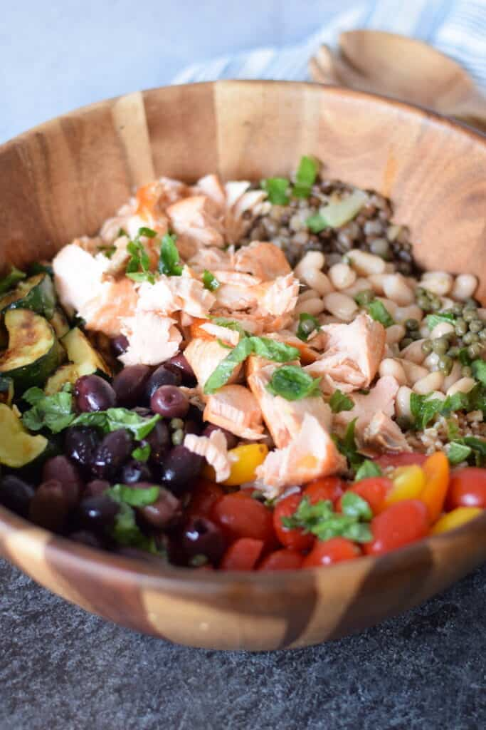 salmon grain bowl in a wooden bowl with serving utensils