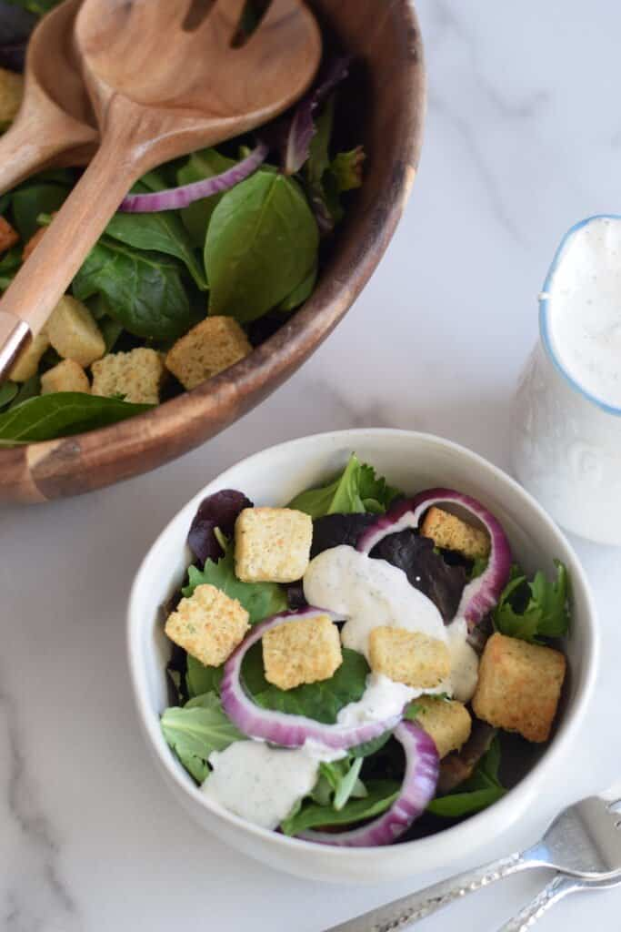 buttermilk ranch dressing on a salad in a white bowl